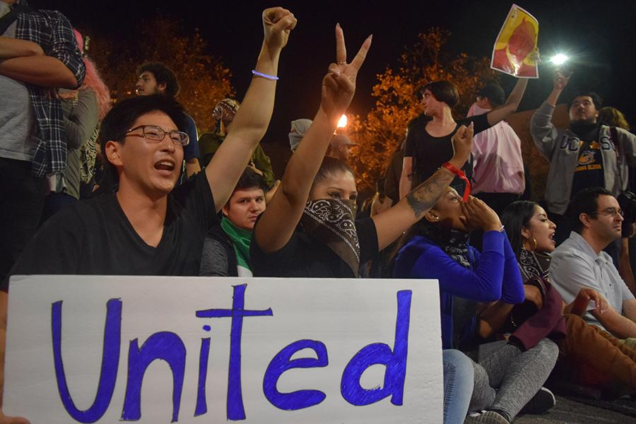 Richmond residents, Ben Choi (left) and Raquel Antolin (right) raise their sit and raise their arms on 8th and Washington in the front line of the #NotMyPresident protest in Oakland, CA on Nov. 9.