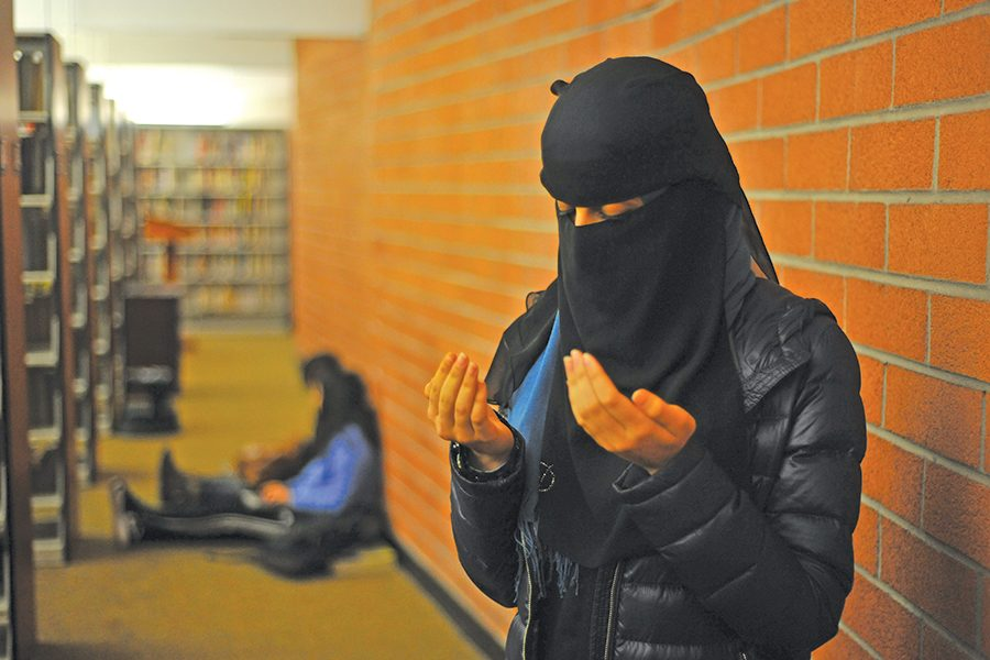 Muslim+student+prays%0Ain+the+behind+the+book-+shelves+in+the+Library+on+March+20.+The+Muslim+Student+Association+is+coordinating+efforts%0Ato+create+a+designated+space+for+praying.