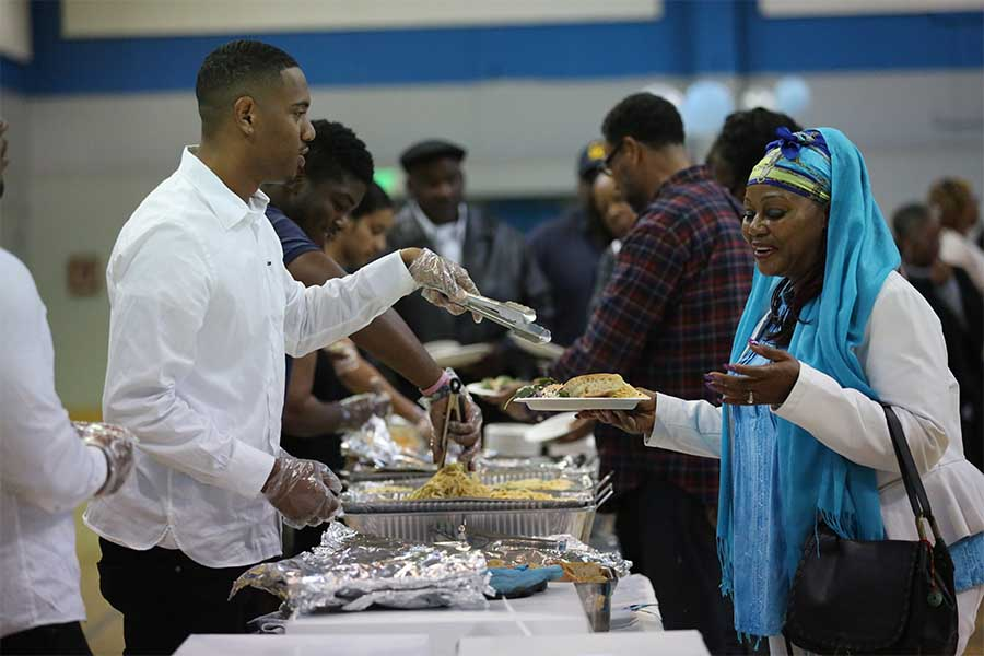 cody casares / The Advocate Liberal arts major Troy Hearne fills West Contra Costa Unified School District sixth grade teacher Verdell Simon-Tatum's plate during the annual all you can eat Crab Feed event in the Gymnasium on Saturday. The fundraiser encourages attendees to feast on crabs, pasta and bread.