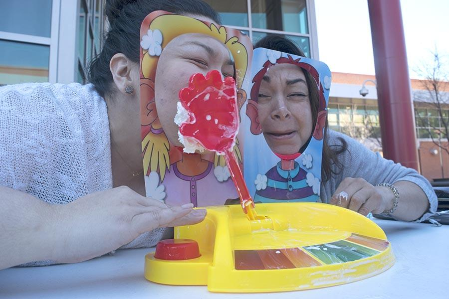 HSI STEM Manager Mayra Padilla (right) and  (left) WAVES club adviser Kelly Ramos play the game Pie Face Showdown during the Women Advancing Via Engineering and Science (WAVES) club fundraising event in the Campus Center Plaza on Tuesday.