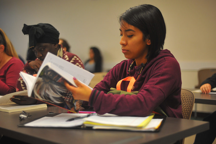 Medical assistant major Diana Lapop flips through pages of the Anthropology of Religion, Magic and Witchcraft textbook during an Anthropology 150 class session in GE-311 on Thursday. The class reviewed witchcraft in European villages.