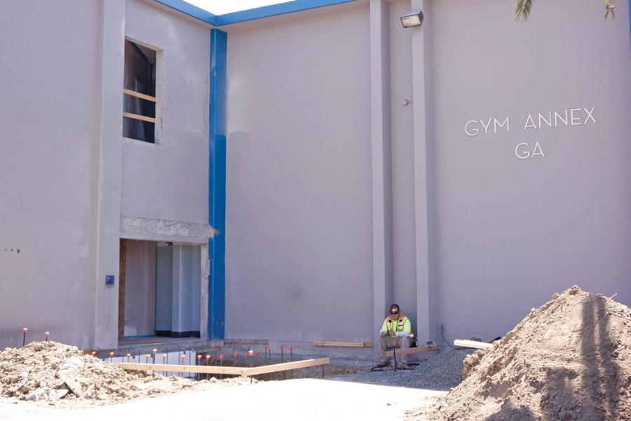 A construction workers sits outside the Gym Annex Building on Monday. An external lift is being installed after spending years in planning limbo due to a lack of state funding.