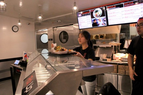 Two employees at Koja Kitchen in Berkeley serve up dishes on Sept. 17.