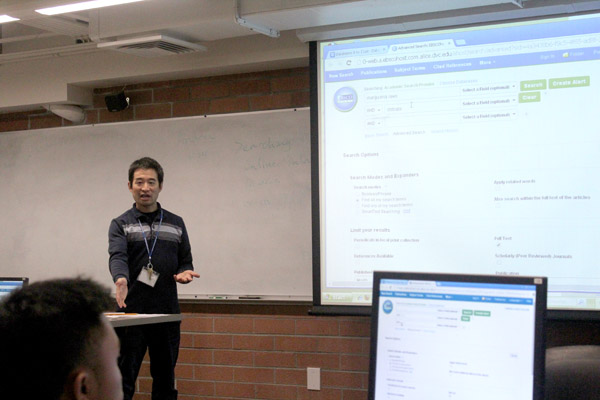 Library department Chairperson Andrew Kuo (center) explains search phrases while nursing major Elijah Fernandez (left) looks on during the