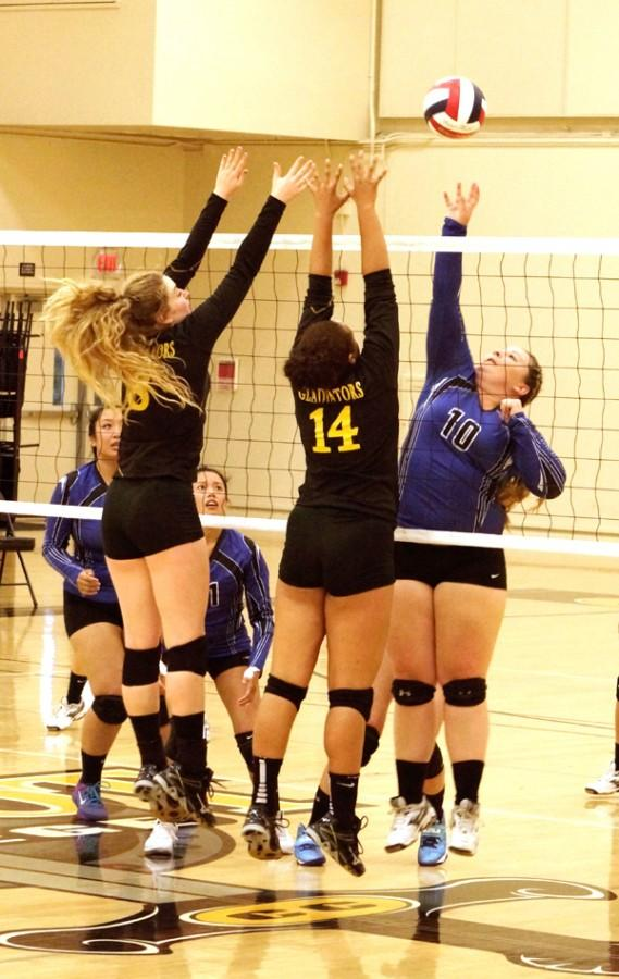 Comet outside hitter Kailey Walker (right) attempts to loft the ball over the net toward Gladiator players Krissa Marie San Juan (left) and Mary Newman (middle) during CCC's loss to Chabot College in Hayward on Sept. 10.