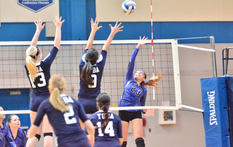 Comet outside hitter Rachelle Cuevas (right) attempts to loft the ball over the net toward 49er outside hitter Victoria Helm during CCC's loss to Yuba College in the Gymnasium on Friday.