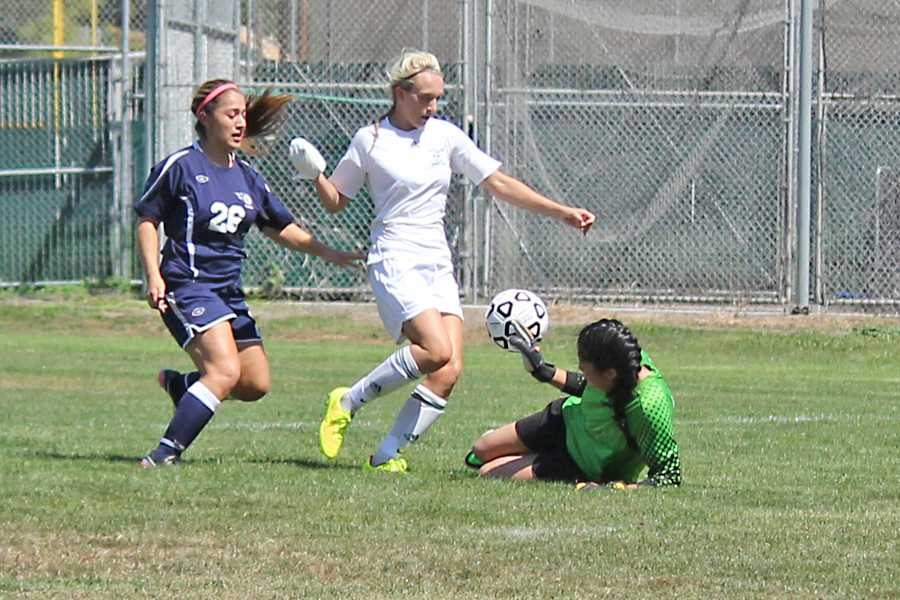 Knights' forward Megan Williams (middle) takes a shot on goal over the Comet goalkeeper Christy Garcia (right) to earn the Knights their second goal during the first half of CCC's 4-2 loss to Shasta College on the Soccer Field on Aug. 27.