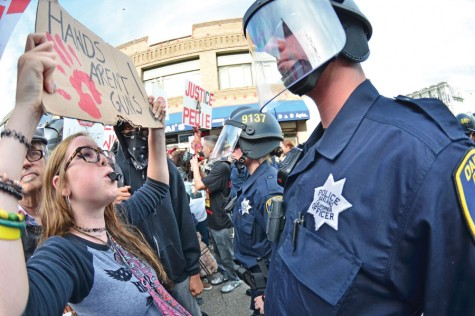 Protester Darla Sorensen, an Oakland Technical High School student, confronts an Oakland police officer as she marches toward the Oakland Police Department during the National Day of Protest Against Police Brutality in Oakland on Oct. 22.