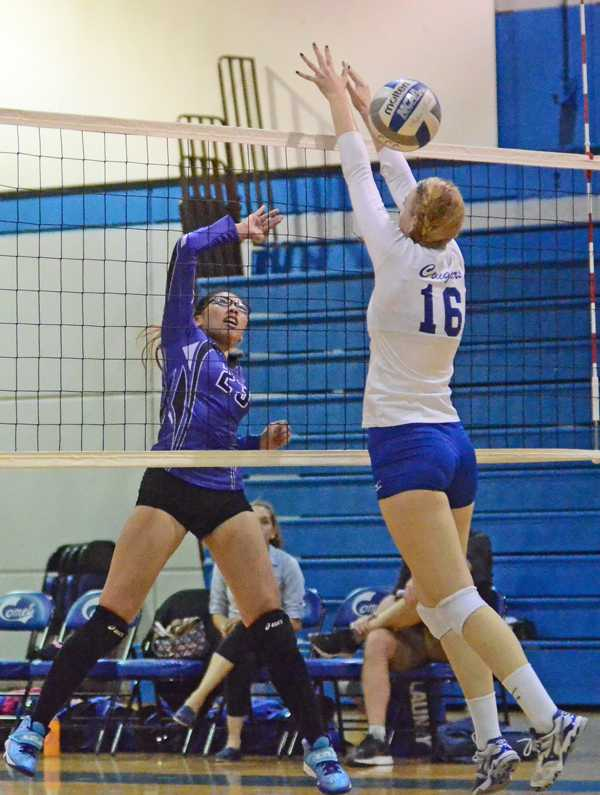 Comet outside hitter Rachelle Cuevas (left) spikes the ball past Cougar middle blocker Nadia Bedard (right) during CCC's loss to College of Alameda in the Gymnasium on Friday.