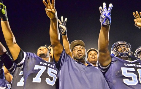 Coach Alonzo Carter (center) points toward their conference banner in the stands after the Comets' 51- 10 win over San Jose City College at Comet Stadium on Saturday, Nov. 15, 2014.  The win clinched the  team's third  consecutive conference championship.