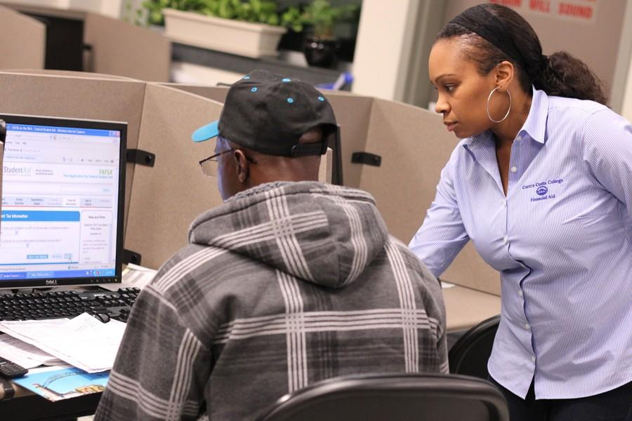 Financial aid assistant Shana Hall (right) helps a student with his financial aid application in the Assessment Center in the Student Services Center on Feb. 18.