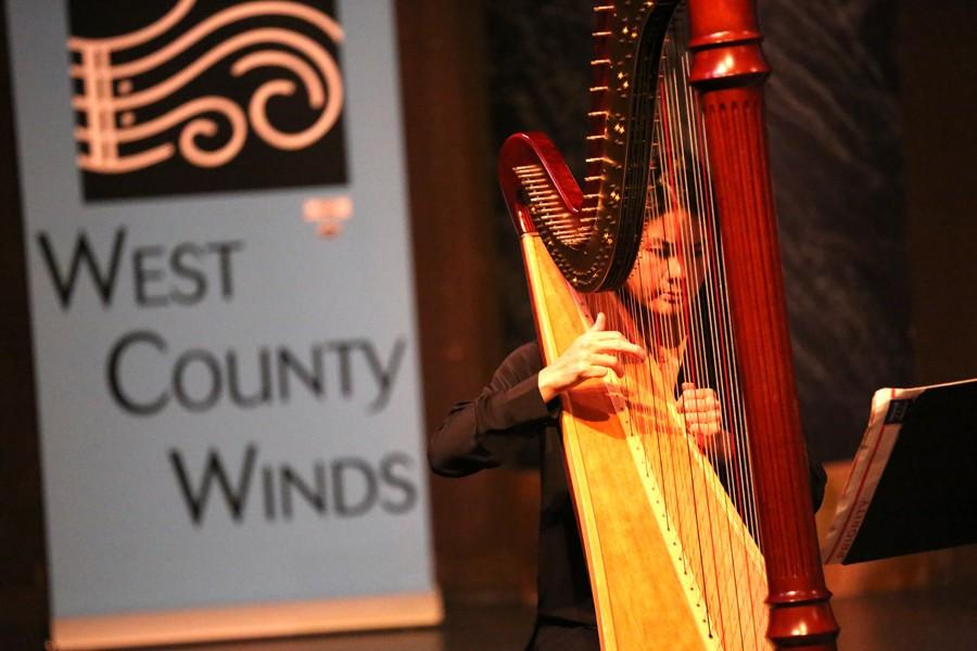 Guest harpist Constance Koo precisely strums her instrument during the West County Winds musical performance organized by the music department in the Knox Center on Sunday.
