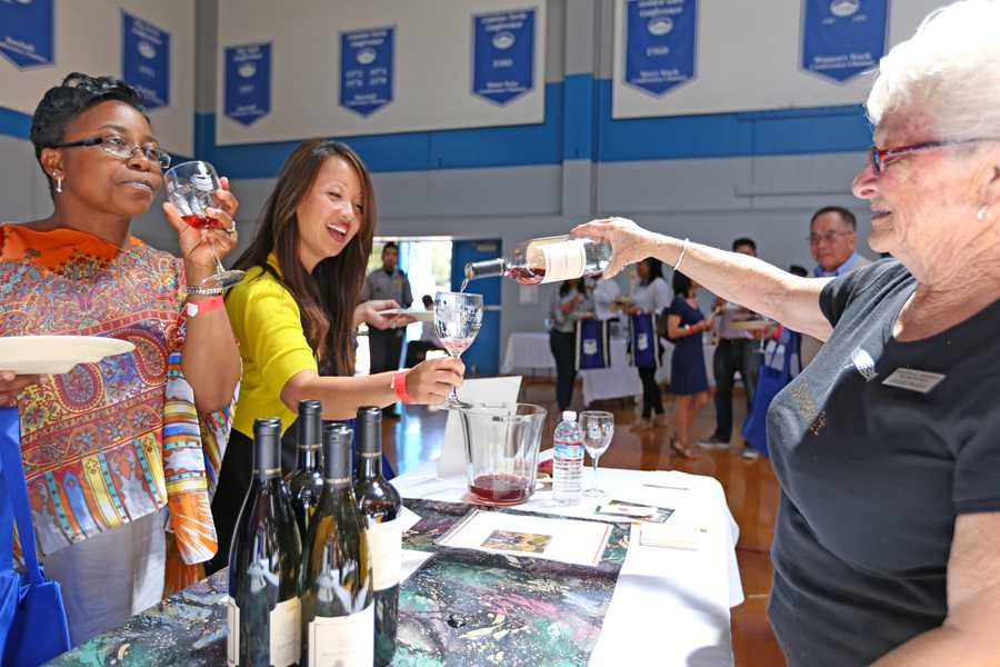 Arlene Passini, Monticello Vineyards employee, pours a glass of red wine for Tammeil Gilkerson, vice president (center), and Vicki Ferguson, dean of student services (left), during the 8th Annual Food and Wine Event held in the Gymnasium on Sunday.