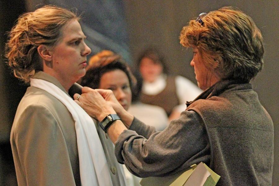 "Kelly Ground (right), director of ""Silent Sky,"" makes final alterations to Henrietta Leavitt's (Clove Galilee) coat during a dress rehearsal in the Knox Center on Thursday."