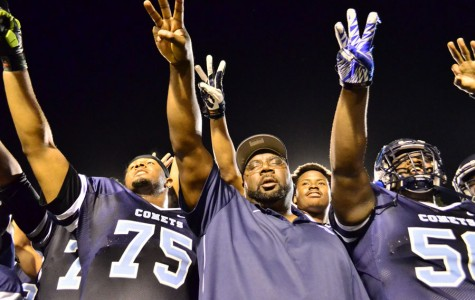 Coach Alonzo Cater (center) points toward the team's championship banner in the stands after the Comets' 51-10 win over San Jose City College at Comet Stadium on Nov. 15, 2014. The win clinched the team's third consecutive conference championship.