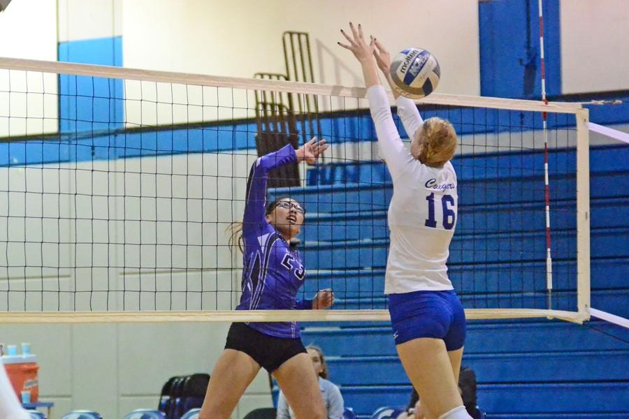 Comet outside hitter Rachelle Cuevas (left) spikes the ball past Cougar middle blocker Nadia Bedard (right) during CCC's loss to College of Alameda in the Gymnasium on Oct. 24, 2014.