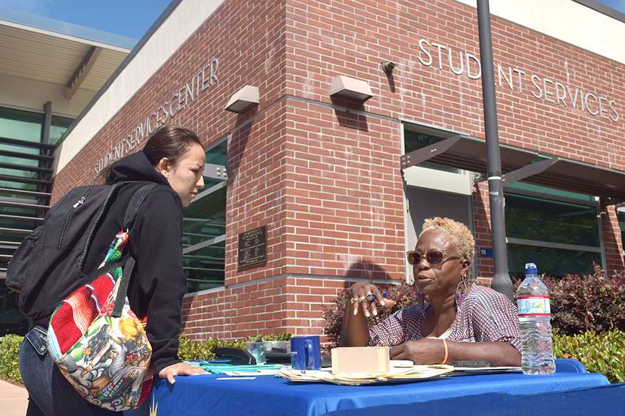 Student Raquel Garcia speaks to Supported Education Services coordinator Anntheia Farr during Constitution Day at the Student Services Center Plaza on Thursday.