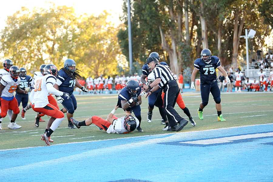 Comet running back Robert Wilkes plows over Tiger linebacker Clay Jones and into the end zone during Contra Costa College's 37-28 win against Reedley College on Saturday at Comet Stadium.
