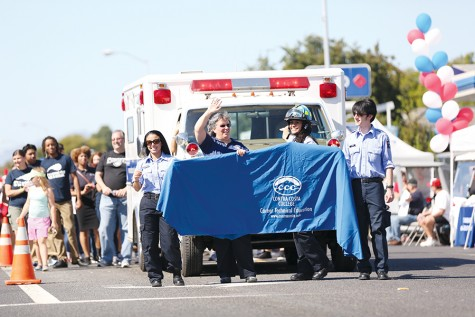Contra Costa College volunteers wave to spectators during the parade at the El Sobrante Stroll on San Pablo Dam Road on Sunday. CCC showcased its ambulance followed by a trail of students and faculty.