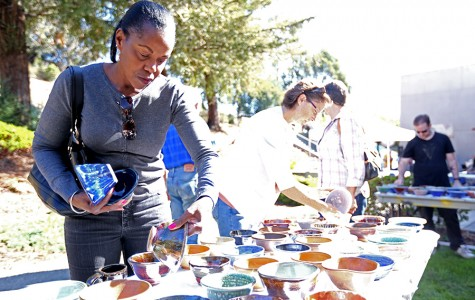 Local resident Denise Maloney examines a bowl during the Empty Bowls project event at the Applied Arts Building Patio outside of the Three Seasons Restaurant on Friday.