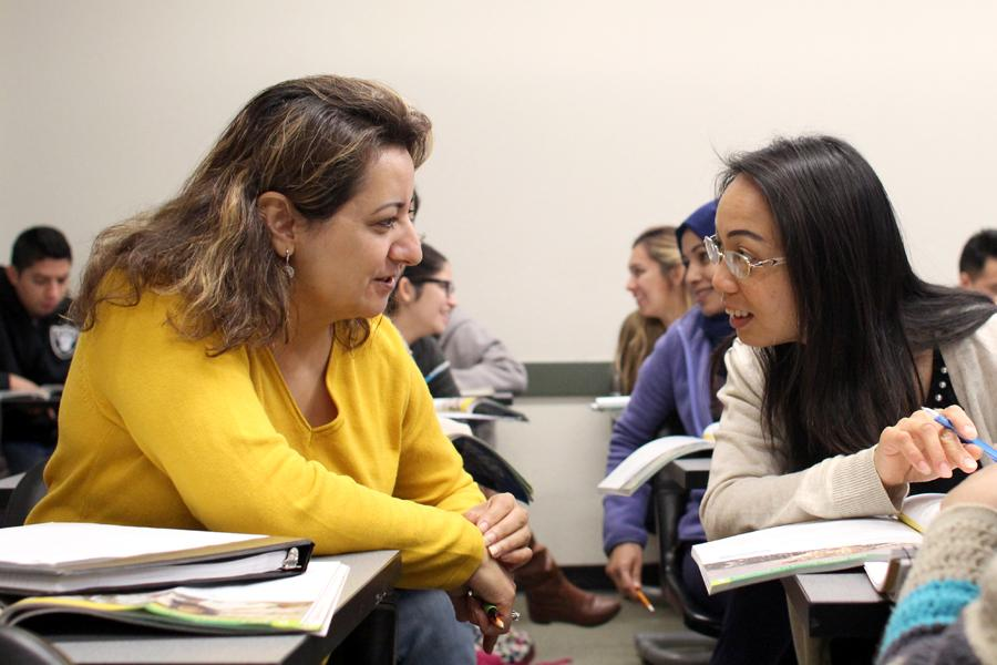 (Left) Nadia Shamil, from Afghanistan, collaborates with Amy Chen, from China, on a group assignment during an ESL 126 class in LA-106 on Monday.