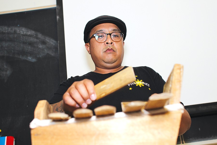 Mathematics professor Edward Cruz plays a Gabbang  during the Filipino Heritage Month event held by the Filipino American Student Union in B-12 on Friday.