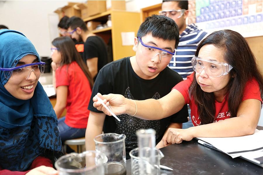 ABOVE: Dr. Seti Sidharta, winner of the 2015 Golden Apple Award, oversees a copper cycle experiment in which students mix copper metals with chemical reagents to create color compound reactions in PS-6 on Monday.