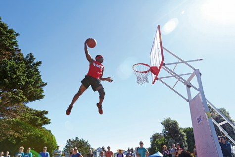 Elandis Brooks of Showtime Dunk launches into the air off a small trampoline to dunk the ball during the Richmond Home Front Festival at Marina Bay Park on Saturday.