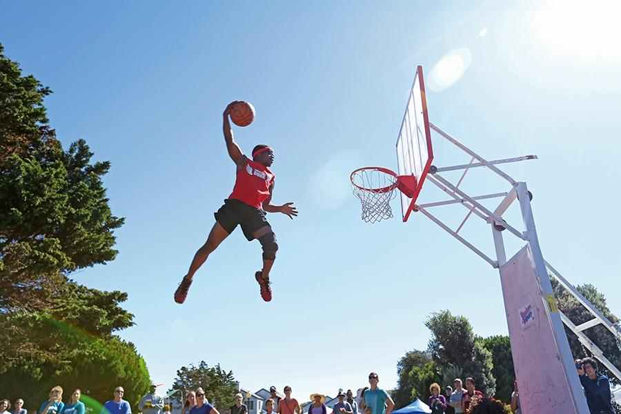 Elandis+Brooks+of+Showtime+Dunk+launches+into+the+air+off+a+small+trampoline+to+dunk+the+ball+during+the+Richmond+Home+Front+Festival+at+Marina+Bay+Park+on+Saturday.