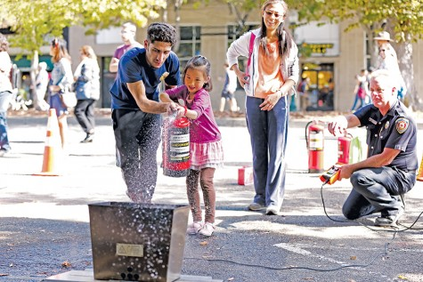 Berkeley High School student volunteer Nehar Ali chaperons Wendy Xia's daughter as she quells a simulated trash can fire during the Sunday Streets event on Shattuck Avenue in Berkeley Sunday. The demonstration was provided by the Berkeley Fire Department.