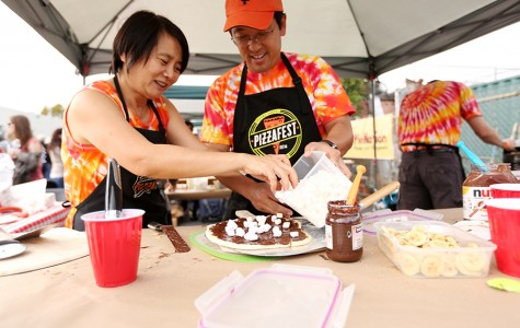 Nu-Nhi Nguyen (right) and Ken Mikami from World Traveling Pizza Makers garnish a pizza with marshmallows for their Smores pizza during Pizzafest in Berkeley on Sunday.