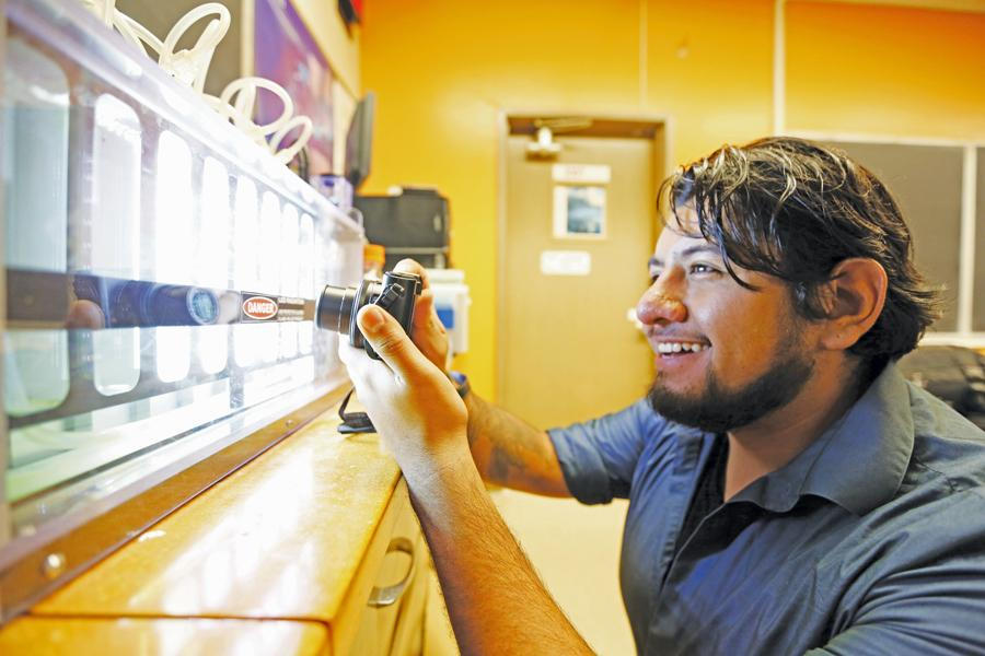 Biotechnology major Ray Serafin takes a photo of a bioreactor that cultivates algae in B-18 at Contra Costa College in San Pablo, Calif. on Monday, Oct. 26, 2015. Serafin is interested in capturing scientific procedures and enjoys displaying his photos for the public.