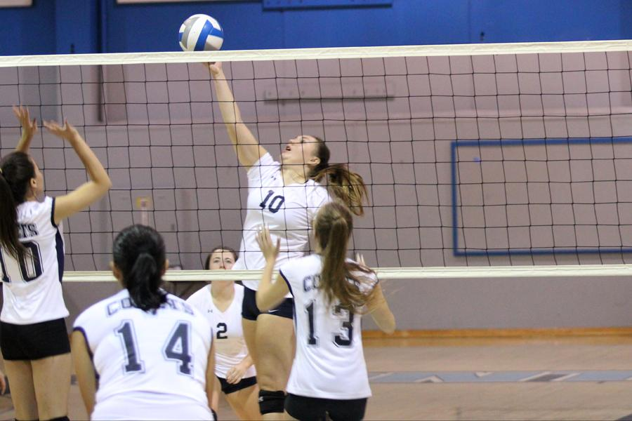 Eagle outside hitter Jamie Mertle tips the ball over the net and Comet middle blocker Mariah Marinho (left) during the game against Mendocino College on Friday in the Gymnasium.