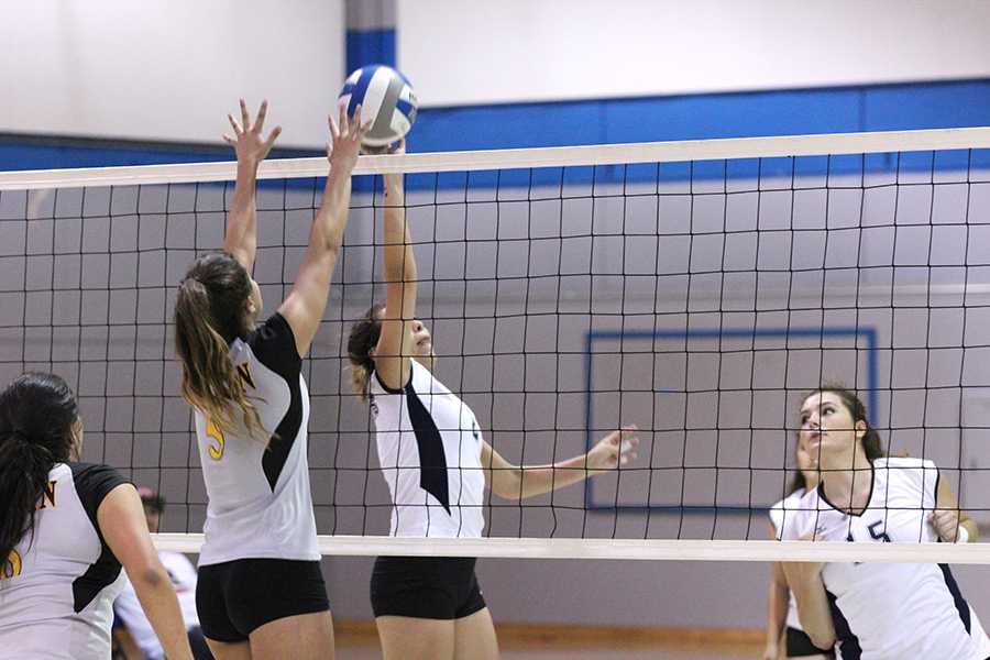Comet striker Paula Sanchez (middle right) defends against Mariner striker Jenny Huezo during the volleyball team's loss to Marin on Friday.