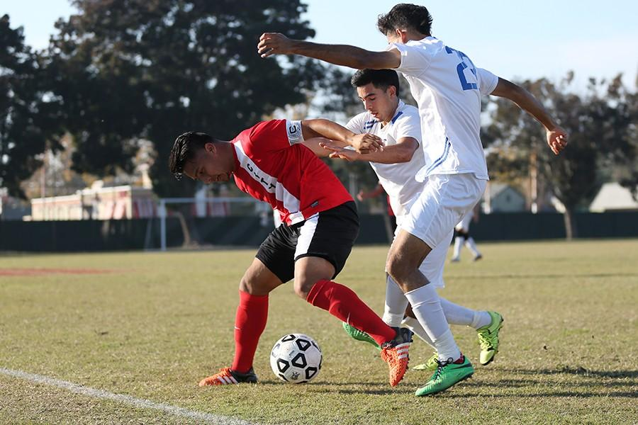 Ram midfielder Sergio Segura shields the ball from Comets Pedro Rodriguez and Alejandro Gonzalez during Contra Costa College's playoff game against Fresno City College at Fresno City College on Nov. 21.