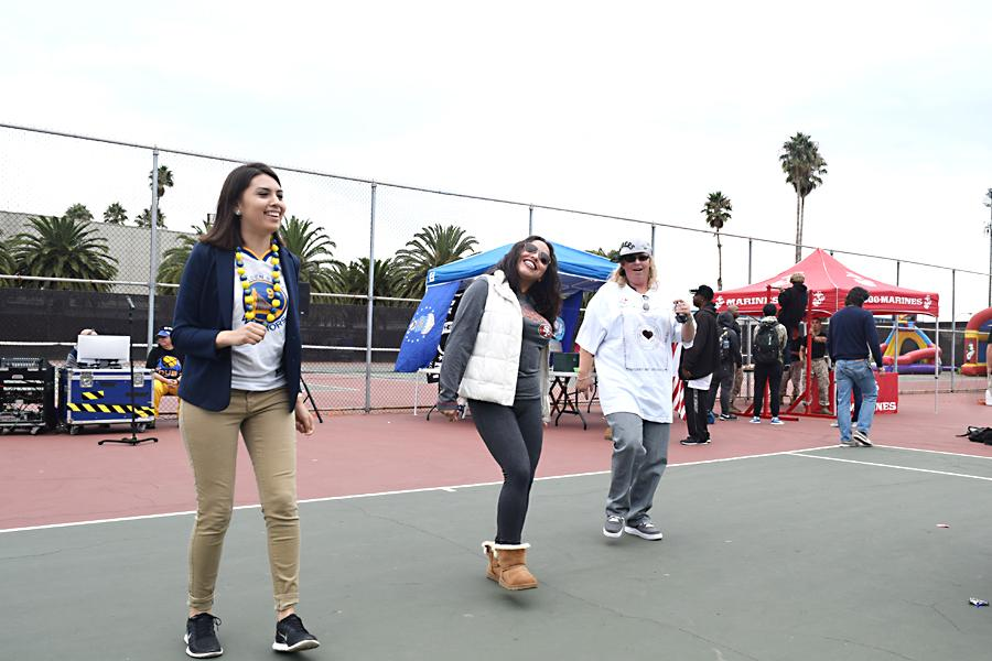 Law Club President Nora Rodriguez (left) dances with other participants in front of the Law Club stand during the all-sports themed Club Rush event at the Tennis Courts on Oct. 27 and 28.