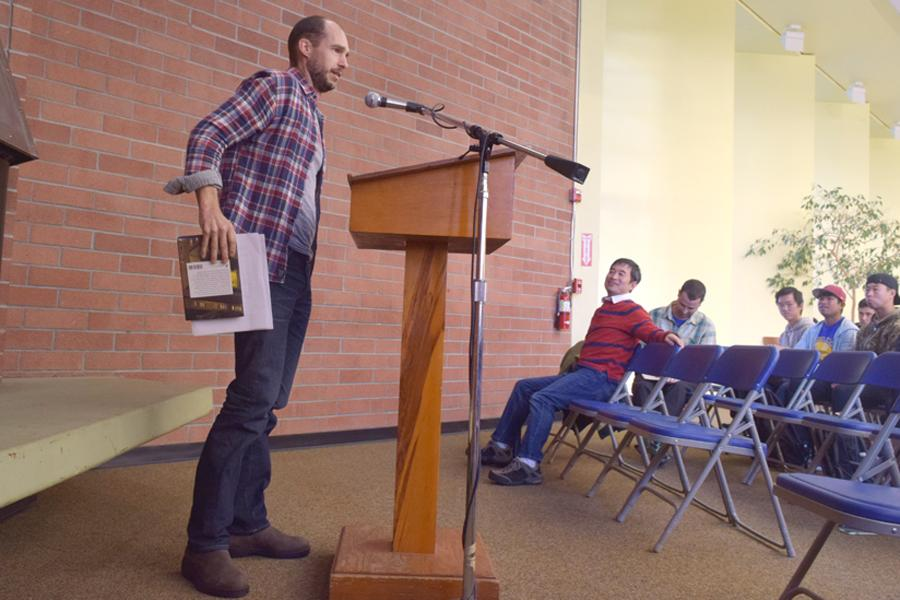English professor Benjamin Jahn presents a scene from his fiction novel during the poetry reading and open mic event in the Library and Learning Resource Center on Nov. 3.