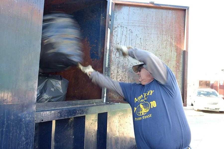 Buildings and Grounds worker Mike Mayo tosses a bag of garbage into a trash compactor located behind the Baseball Field on Monday. The compactor saves Buildings and Grounds $375 per month.