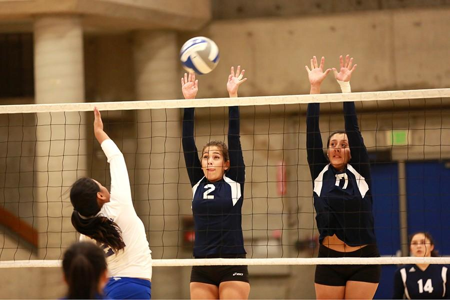 Comet setter Paula Sanchez (left) and middle blocker Alejandra Galvez attempt to block the ball hit by a Cougar  defensive specialist during Contra Costa College's 3-0 loss in Alameda on Friday.