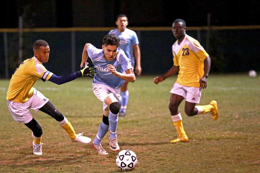 Comet defender Edgar Yepes (center) fools Thunderbird defender Shishay Sebatu (left) by cutting to the outside during Contra Costa College's 3-1 win against Merritt College on Friday. Yepes has started 19 games this season, including 11 conference games.