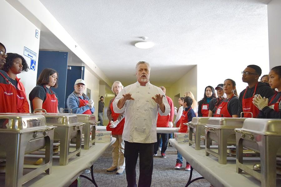 Bay Area Rescue Mission culinary arts manager Chris Dikes talks to the volunteers and staff before serving the food, giving words of motivation in a hallway at the Richmond Civic Center during the annual Great Thanksgiving Banquet sponsored by the Bay Area Rescue Mission.