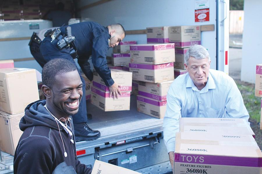 Police Services Officer Charles Hankins (left) and Buildings and Grounds Manager Bruce King help upload toys for the sixth annual Toy Drive by the Parking Annex close to Castro Road on Friday.