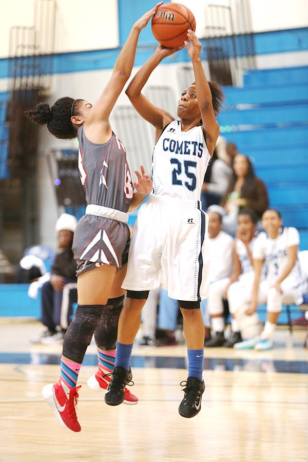 Owl guard A.J. Leasau blocks a shot by Comet guard Tynisha Adams during the Contra Costa College  Classic  at the Gymnasium on Dec. 6.