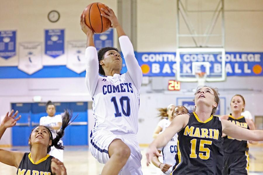 Comet+guard+Jacqie+Moody+goes+up+for+a+layup+against+Mariners+guard+Janelle+Pansoy+and+foward+Christiana+Onwuasoeze+during+Contra+Costa+Colleges+80-57+win+against+College+of+Marin+in+the+Gymnasium+on+Friday.