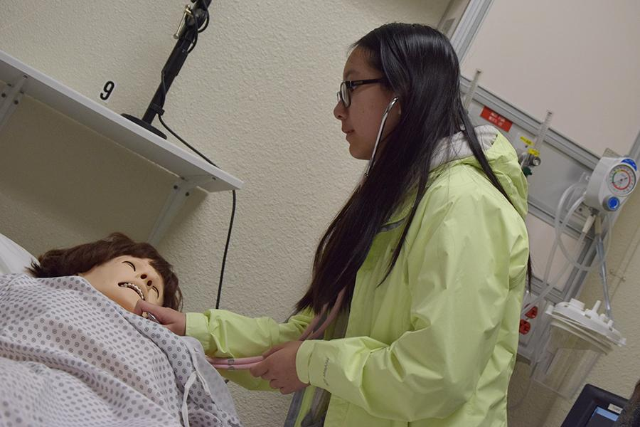 Evelyn Statford a high school student uses a stethoscope to hear the heartbeat of a life-size robotic patient in HS-107 during Health Services Day on Friday.