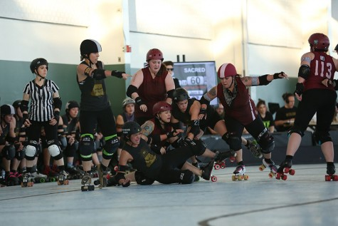 Shengis Khan (lower center) takes a spill during the B.A.D United Double Header at the Craneway Pavilion on Saturday. The skaters wear full body protection with falls being a regular occurrence and pushing, shoving and blocking being the main strategy of the game.