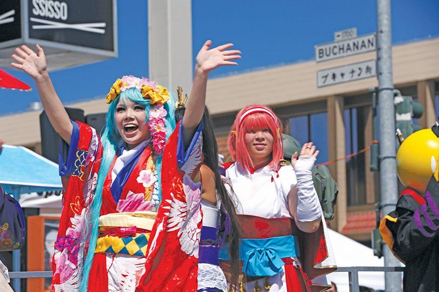 Parade participants riding the Anime Costume Parade group float wave to bystanders during the Northern California Cherry Blossom Festival on Polk Street in San Francisco on Sunday.