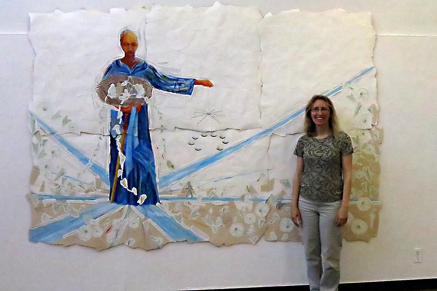 "Artist Kim Vanderheiden stands with one of her paintings, ""Lady Justice,"" in the Eddie Rhodes Gallery on March 17. The exhibit ""Working from the Torn Things"" will be displayed until April 15."