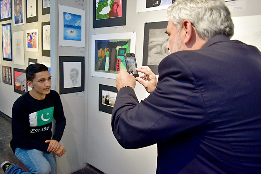 High school student Mian Jalal (right) poses next to his pencil drawing as Richard Ambrose, RAC executive director, takes a picture with his cellphone during the WCCUSD Student Art Show at the Richmond Art Center on Thursday.