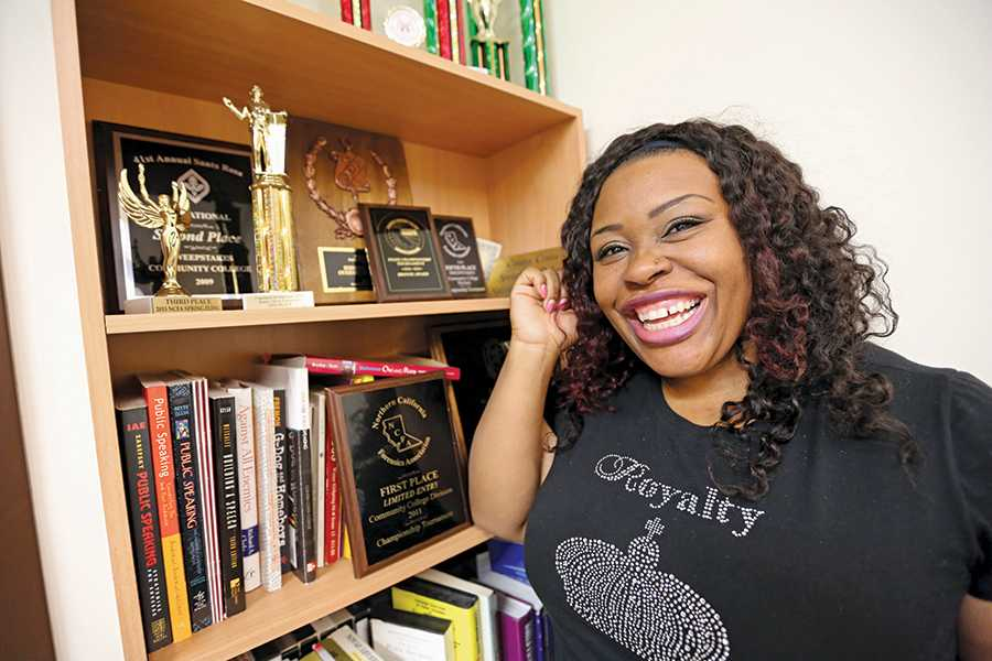 Communications major Lerecia Evans-Davis poses next to awards won by the speech department in the AA Building. Evans-Davis is a key asset on the speech and debate team, gaining various accolades at speech tournaments.